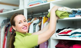 Woman arranging clothes at wardrobe