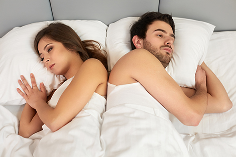 Upset couple lying back to back in bed