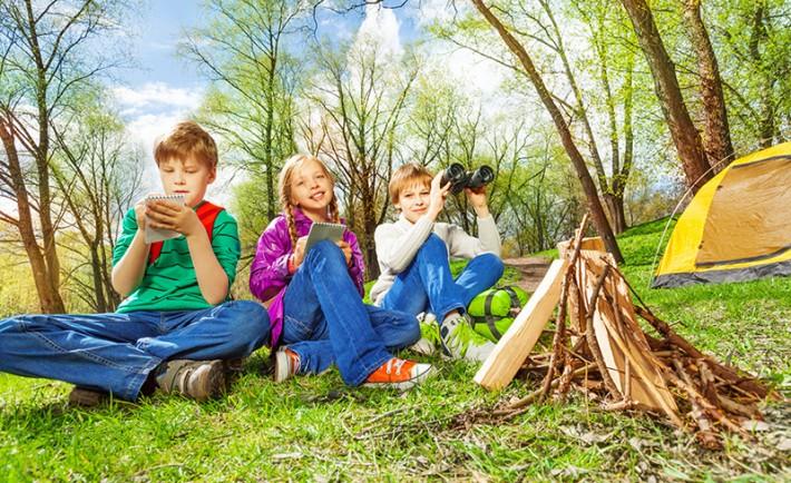 Three children resting near the wooden bonfire